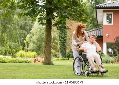 A senior woman in a wheelchair with her private professional caretaker outside in the garden during summer day.