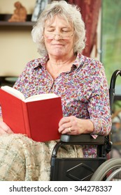 Senior Woman In Wheelchair Reading Book