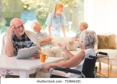Senior woman in a wheelchair talking to her friend while sitting at a table in common room