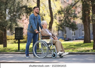 Senior woman in wheelchair with young man at park