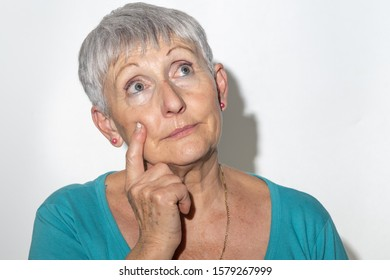 senior woman with White hair and blue eyes in thoughtful expression