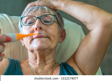 senior woman with white hair and glasses with one hand on her head and the other with a thermometer