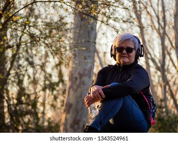A senior woman with white hair listening to music with headphones and a plastic water bottle in her hand