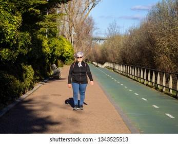 A senior woman with white hair listening walking in an urban park