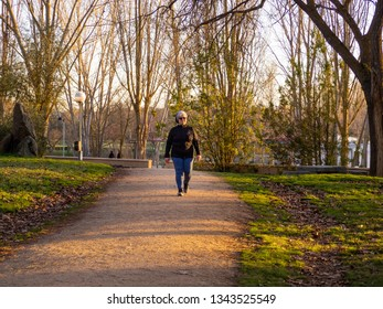 A senior woman with white hair listening to music with headphones walking in an urban park