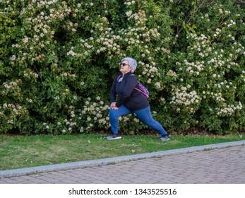 A senior woman with white hair practicing gymnastics in an urban park