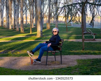 A senior woman with white hair practicing gymnastics in a bio-healthy park