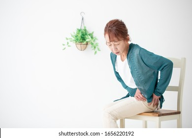 The senior woman who has a pain in her hip joint