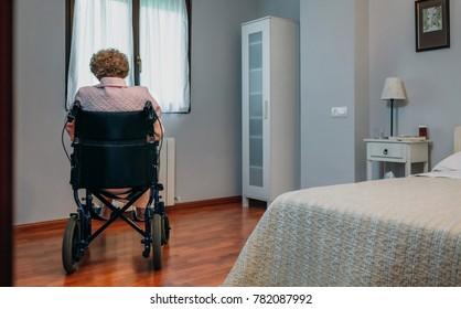 Femme âgée en fauteuil roulant seule dans une chambre
