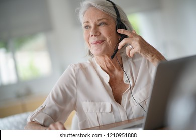 Senior woman working on computer with headset