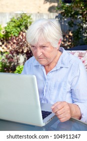 A senior woman working on her laptop computer.