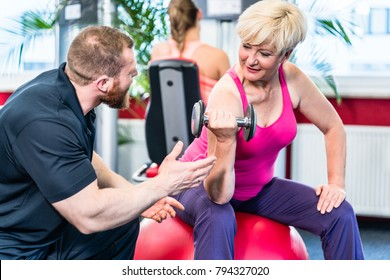 senior woman working out with dumbbells with personal trainer at gym