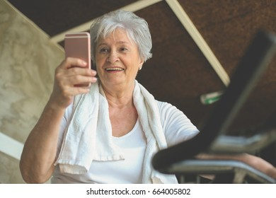Senior woman working out in gym sitting on elliptical machine and typing on smart phone.