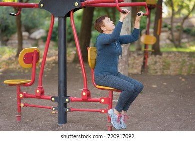 Senior woman working out on the sports public equipment in the outdoor gym.A sportive active elderly woman doing physical exercise in a park at sunny day.