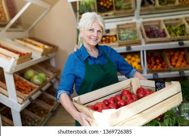 Senior woman working in small grocery store