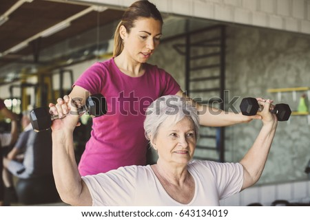 Senior woman workout in rehabilitation center. Personal trainer helping senior woman