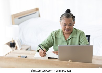 senior woman writing in notebook and using laptop computer at home