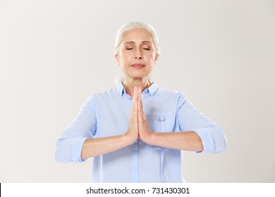 Senior woman practi?ing yoga holding hands in namaste and keeping her eyes closed, isolated on white background