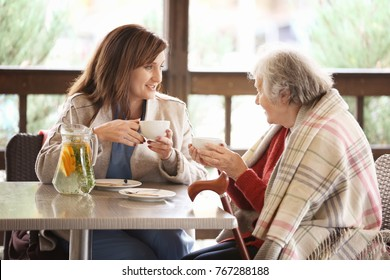 Senior woman and young caregiver drinking tea at table in cafe
