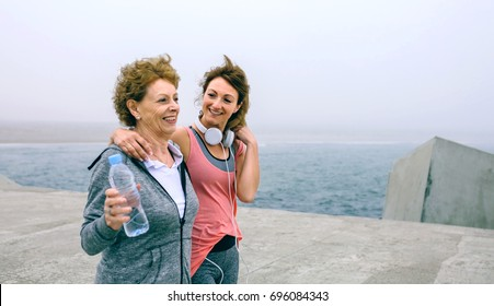 Senior woman and young woman walking outdoors by sea pier
