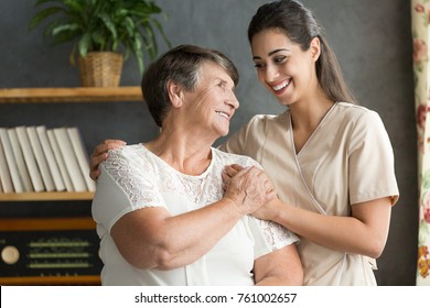 Senior woman and younger friend having fun together during meeting at home