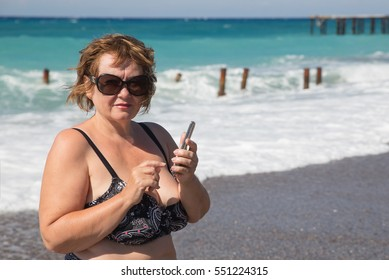Senior womanphotographing by telephone at beach