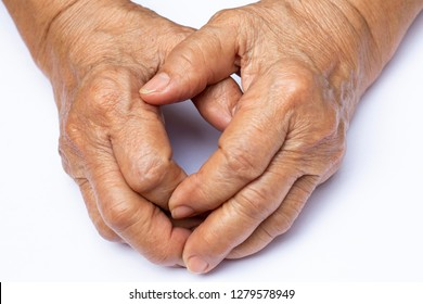 Senior woman's grasping her hands, wrinkled skin texture of blood in back of the hands on white background , Close up & Macro shot, Selective focus, Body part, Healthcare concept
