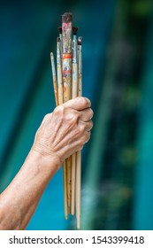 Senior woman's hand holding old paintbrushes in bokeh blue swimming pool background, Selective focus, Hobby paint art concept