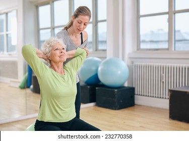 Senior women doing light pilates workout for back muscles with coach assistance. Trainer helping senior woman exercising at gym.