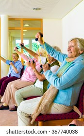 Senior women doing a workout in a gym for old-age pensioners sitting in their chairs doing stretching exercises with elastic bands to improve mobility and strength in their arms