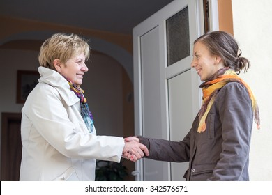 Senior women greeting young girl in the doorway