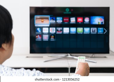 senior women hand hold remote control of TV box watching in the living room