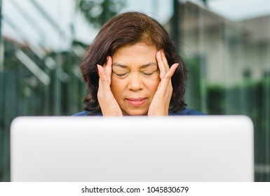 Senior Women with a headache.Mature woman sitting and touching her head with her hands while having a headache pain and feeling unwell after work.
