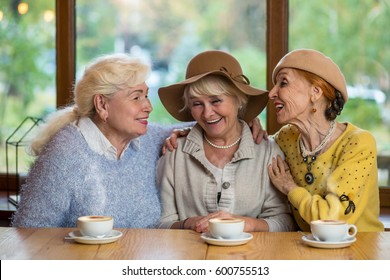 Senior women laughing at table. Happy ladies in cafe. Friendship tested by years.