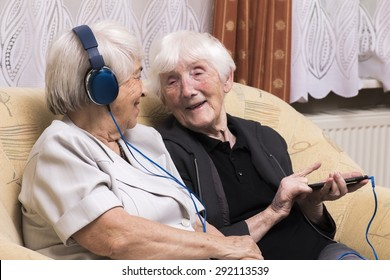 Senior women listening music with headphones at home