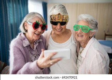 Senior women wearing novelty glasses taking selfie through smart phone at nursing home