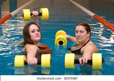 A senior women and young woman in water with dumbbells
