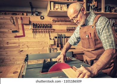 senior woodworker with tablesaw in his workshop