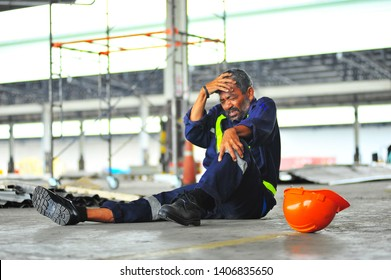 Senior worker accident fall of the scaffolding and headache with broken leg in construction site health insurance concept.