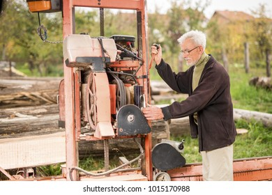 Senior worker cutting wood outdoors