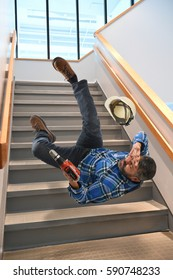 Senior worker falling on stairs while holding cordless drill