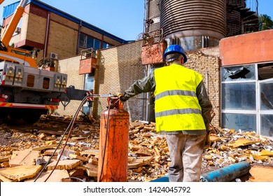 Senior worker in gloves with blue helmet and safety waistcoat is preparing gas welding equipment for cutting scrap metal, cylinders with LPG and Nitrogen, acetylene torch.