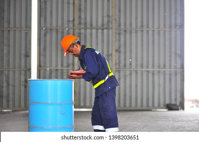 Senior worker inspecting chemical drums in warehouse.