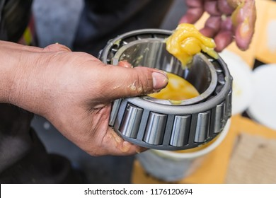 Senior worker putting lubricant lithium grease (NLGI 3) into wheel bearing for ten wheel truck car by hand at service station in Asia. Grease appearance is yellow. Maintenance and preventive concept.