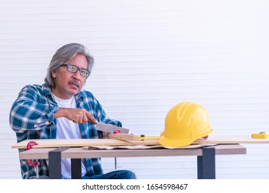 Senior worker is saw on wood workshop table for home improvement project