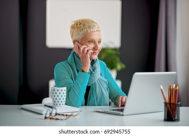 Senior worker sitting at the desk in modern office and doing multitasking