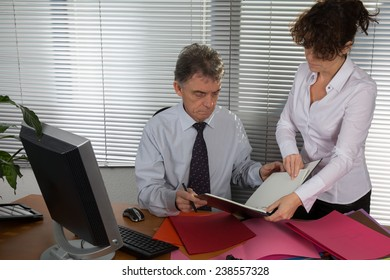 senior working man  and a secretary discuss something during their meeting,