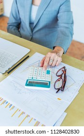 senior working woman touching calculator with eyeglasses and report data on wood desk in office.