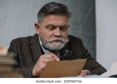 senior writer reading manuscript with magnifying glass