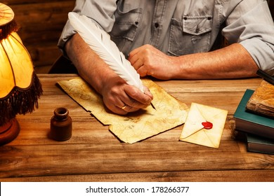 Senior writing letter with quill pen in homely wooden interior